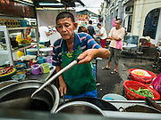 "15 NOVEMBER 2016 - GEORGE TOWN, PENANG, MALAYSIA: A street food vendor makes fried rice on Kimberly Street, one of George Town's better known ""food streets."" George Town is a UNESCO World Heritage city and wrestles with maintaining its traditional lifestyle and mass tourism.           PHOTO BY JACK KURTZ"