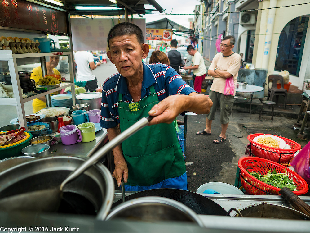 """15 NOVEMBER 2016 - GEORGE TOWN, PENANG, MALAYSIA: A street food vendor makes fried rice on Kimberly Street, one of George Town's better known """"food streets."""" George Town is a UNESCO World Heritage city and wrestles with maintaining its traditional lifestyle and mass tourism.           PHOTO BY JACK KURTZ"""