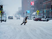 17 JANUARY 2020 - DES MOINES, IOWA: Women cross snow packed Court Street in the Court District neighborhood of Des Moines. The second significant snow fall in a week hit central Iowa Friday. The snow started falling during the morning rush hour and by early afternoon about five inches had fallen in Des Moines. Meteorologists said up to 1/10 of an inch of ice could cover the snow by the end of the day. The snowstorm was expected to turn into a blizzard in northern Iowa on Saturday with wind speeds above 30MPH. Many businesses in the Des Moines area closed early Friday and several of the Democratic presidential candidates cancelled their campaign events because of the snow.    PHOTO BY JACK KURTZ