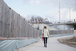 Rear view of a young woman walking along construction site fence on road, Munich, Bavaria, Germany
