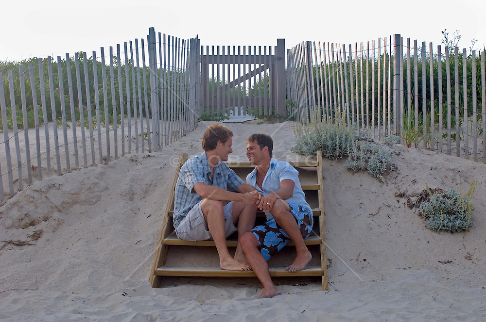 Two men sitting together on steps at the  beach in East Hampton, NY