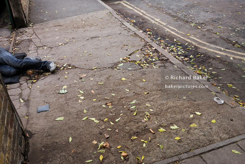 A pair of legs lie oddly at the entrance of a driveway on a London street.