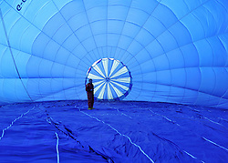 ©London News pictures. 07/04/2011. CANTERBURY: A flyer checks the inside of his balloon. Approximately 50 hot air balloons from across the UK and Europe take advantage of the weather window and take off from Lydden Hill Race Circuit, Wootton, Kent, to fly across the English Channel marking the largest ever group of balloons to attempt the crossing. The participants  have been waiting since October for the event to happen. Picture credit should read Stephen Simpson/LNP