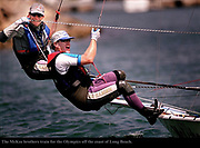 8/24/00 -Helmsman Jonathan McKee,40, (top) takes the line in his teeth whil his brother Charlie McKee,38, both of Seattle, Washington , crews while training for the Olympics in their 49er  class sailboat off the coast of Long Beach on Thursday, August 24, 2000. The brother team will represent the U.S. in the new 49er class sailing races in Sydney next month. <br />Photo by Marilynn Young/Press-Telegram