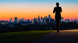 London, October 27 2017. A runner's silhouette contrasts with the early morning light as the day breaks over London's skyline, seen from Primrose Hill. © Paul Davey