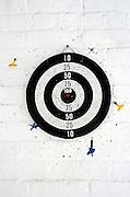 dart board and darts on brick wall
