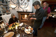 (MODEL RELEASED IMAGE). After making the chilly walk back from the Friday market, Jörg Melander lights a fire and his wife Susanne brings out yogurt spreads, cheese, stuffed olives, peppers, fresh bread, and a Dresden stollen and pours a cup of tea for a friend, Venita Kaleps. Hungry Planet: What the World Eats (p. 138).