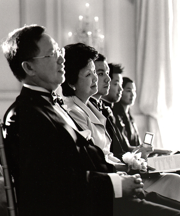 Beautiful B&W photo of Asian family watching their daughter get married at Oheka Castle