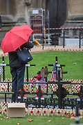 Visitors to the Abbey pause for a look as the hammering goes on - Volunteers from the Royal British Legion set out the Field of Remembrance outside Westminster Abbey. The field comprises thousands of poppies on crosses to remember individuals and units. It will be completed in time for a Royal visit on Thursday . London 07 Nov 2017.
