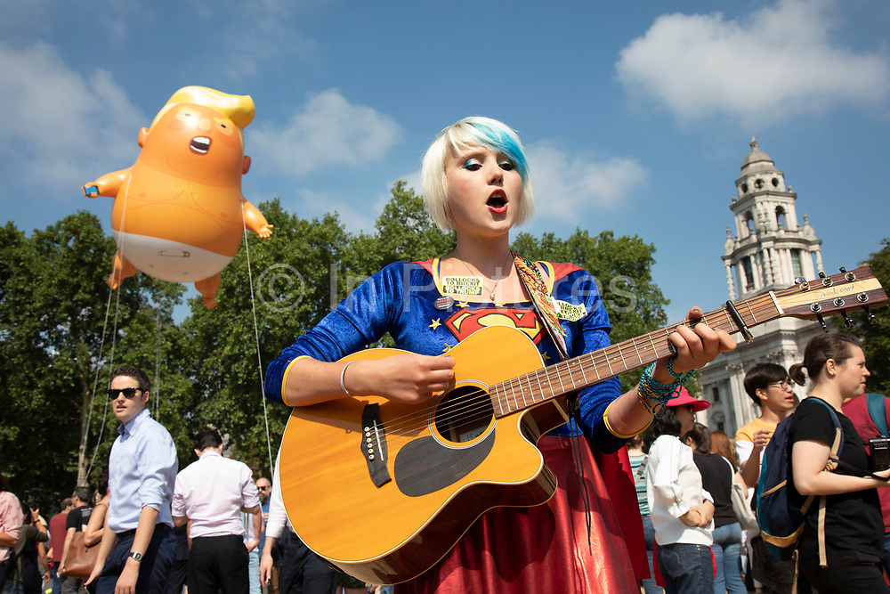 Protest singer and the Trump Baby, a six metre high inflatable blimp flying above the Houses of Parliament in Westminster prior to the Together Against Trump national demonstration on 13th July 2018 in London, United Kingdom. Organisations The Stop Trump Coalition and Stand Up to Trump have come together for a one-off national demonstration to protest against President Trump's policies and politics during his official UK visit.