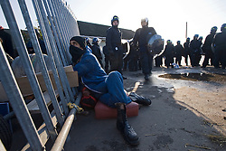 © Licensed to London News Pictures. 19/10/2011. Crays Hill, UK. An activists attached to a fence inside the Dale Farm Travellers Site in front of riot police. Residents at Dale Farm, the UK's largest illegal traveller site being evicted today (19/10/2011) following a long dispute with Basildon Council . Travellers and activist had barricaded themselves in to the site in an attempt to prevent their eviction. Photo credit: Ben Cawthra/LNP
