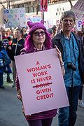 """San Francisco, USA. 19th January, 2019. Aat the Women's March San Francisco, a woman wearing a purple pussy hat with matching purple hair holds a sign reading, """"A woman's work is never (line through done) given credit."""" Credit: Shelly Rivoli/Alamy Live News"""