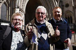 © Licensed to London News Pictures. 23/04/2021. London, UK. Former Post Office sub-postmaster Noel Thomas (C) reacts to the verdict outside The High Court as he stands with his daughter Sian (L) and son Edwin. The Appeal Court is ruling on the convictions of a group of 42 sub-postmasters - some of whom were jailed for stealing money after the Horizon accounting software was installed at Post Offices. At a previous High Court hearing a judge found the Fujitsu accounting system had major faults and defects. The Post Office has already agreed to pay £58m in a settlement with more than 500 sub-postmasters. <br />