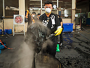 04 NOVEMBER 2016 - BANGKOK, THAILAND:  A volunteer lifts clothes dyed black out of a vat at Krungthai Tractor. About 150 volunteers are working at Krungthai Tractor in Bangkok to dye clothes black for people in mourning following the death of Bhumibol Adulyadej, the King of Thailand. The government declared a one year mourning period, during which Thais are encouraged to wear black and a 30 day mourning period during which Thais are very strongly encouraged to wear black. Furthermore, black is mandatory for official mourning functions, including visits to the Grand Palace and Sanam Luang, the public ceremonial ground across the street from the Palace. The expectation to wear black created a shortage of black clothes in many markets and Thailand's poor couldn't afford what black clothes were still available. Community groups have started dyeing clothes for people who either can't find or can't afford black clothes. The clothes dyeing volunteers at Krungthai Tractor were organized by Thai actress Chompoo Araya A. Hargate and Thai fashion blogger Chavaporn Laohapongchana.     PHOTO BY JACK KURTZ