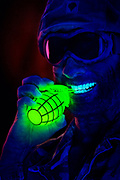 Soldier pulls the pin of a glowing grenade with his teeth.Black light