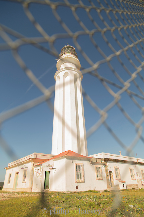 Lighthouse seen through fence, Cadiz, Andalusia, Spain