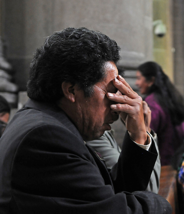 Apr 21, 2011 - Quetzaltenago, Guatemala - Sitting in the Cathedral before the Procession of the Just Judge a man takes a few moments to pray as many other people enter the Cathedral for mass. The Procession of the Just Judge will take the Saint Statues to the President of the Nazarene brotherhood's home, before being brought back to the Cathedral Friday..(Credit Image: © Josh Bachman/ZUMA Press)