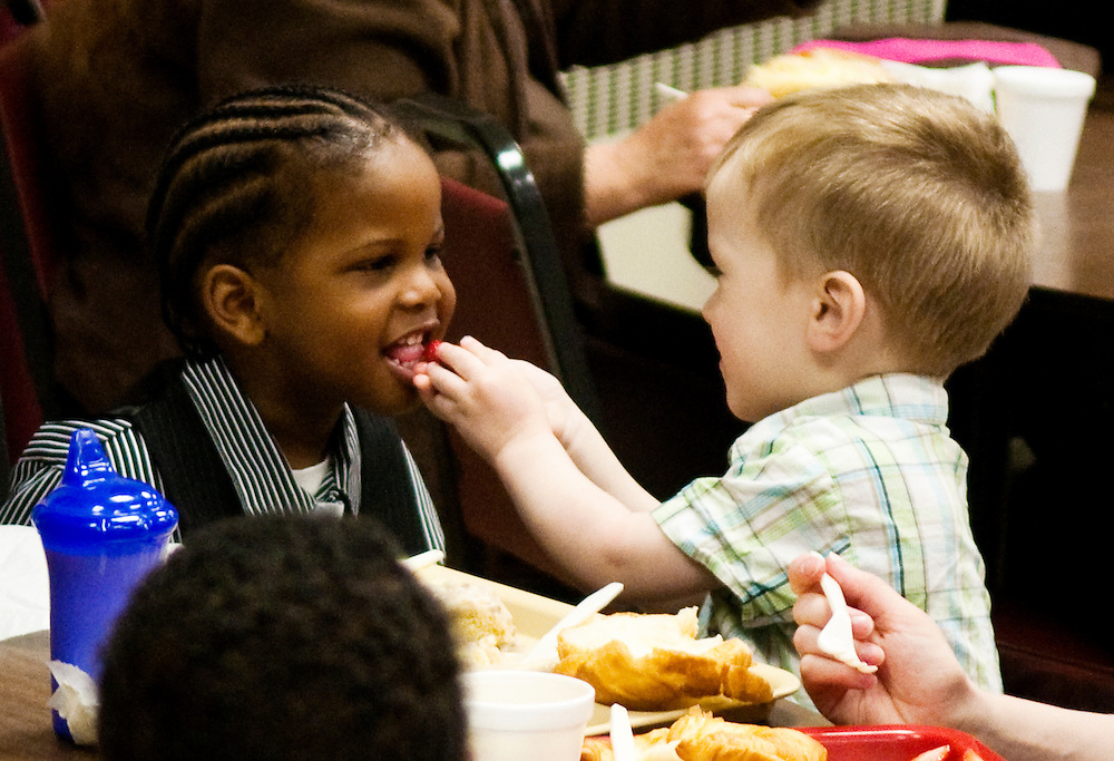 Matt Dixon   The Flint Journal..Dominic Kersjes, 2, of Tennessee feeds his new friend Ny'Aidre Coleman, 3, of Flint a strawberry during breakfast at Carriage Town Ministries in Flint after a special Easter service early Sunday morning. The 7 a.m. sunrise service which was originally intended to be held outdoors was moved inside due to weather conditions.