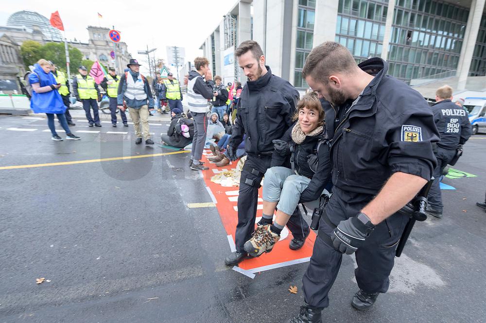 11 OCT 2019, BERLIN/GERMANY:<br /> Eine Demonstration wird von Polizisten waehrend der Aufloesung einer Sitzblockade von Extinction Rebellion (XR), eine globale Umweltbewegung, Weggetragen. XR protestiert mit der Blockade von Verkehrsknotenpunkten fuer eine Kehrtwende in der Klimapolitik, im Hintergrund die Kuppel des Reichstagsgebaeudes, Marschallbruecke<br /> IMAGE: 20191011-01-006<br /> KEYWORDS: Demonstration, Demo, Demonstranten, Klima, Klimawandel, climate change, protest, Marschallbrücke, Protest