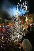 Thousands gather in Westlake Plaza in downtown Seattle to watch the lighting of the Christmas tree and the Macy's star. Fireworks commemorating the 50th anniversary of the star were fired from the roof of Macy's Department Store.<br /> Seattle Times staff photographer