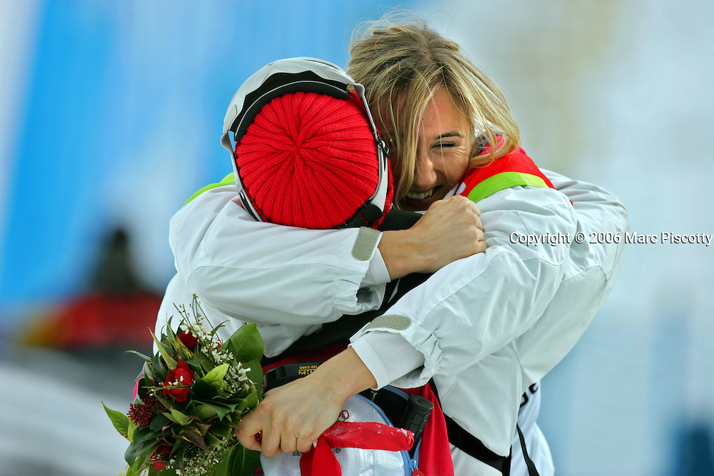 Gold medal winner Tanja Frieden of Switzerland gets a hug from one of her coaches after winning the final race during the 2006 Winter Olympics Women's Snowboard-Cross at Bardonecchia Friday February 17, 2006. U.S. snowboarder and medal favorite Lindsey Jacobellis had a sizable lead over the other three riders in the final run and lost out on a gold medal when she fell trying to showboat off one of the final jumps on the course. Jacobellis had to settle for a silver medal instead with Swiss rider Tanja Frieden taking the gold and Canadian rider Dominique Maltais taking the bronze..(Photo by Marc Piscotty / © 2006)