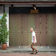 Old man walking past shop front in Luang Prabang
