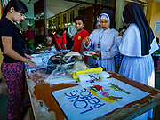 19 NOVEMBER 2017 - HWAMBI, YANGON REGION, MYANMAR: Nuns buy souvenir tee shirts of Pope Francis' visit to Myanmar before mass at Sacred Heart's Catholic Church in Hwambi, about 90 minutes north of Yangon. Catholics in Myanmar are preparing for the visit of Pope Francis. He is coming to the Buddhist majority country November 27-30. There about 500,000 Catholics in Myanmar, about 1% of the population. Catholicism was originally brought to what is now Myanmar more than 500 years ago by Portuguese missionaries and traders.    PHOTO BY JACK KURTZ