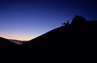 A hiker and tent are silhouetted at dusk while camping in Canyonlands National Park, Utah.