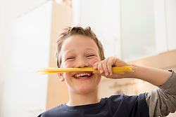 Smiling boy holding spaghetti under his nose