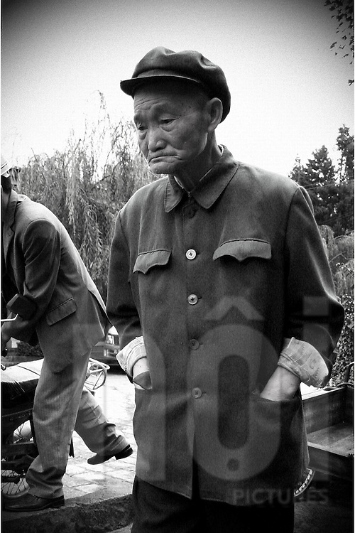 Portrait of an old chinese man in a park. He wears Mao's style flat cap. His face his really wrinkled and he look sad, worried. His puts his hands in his jacket's pockets.