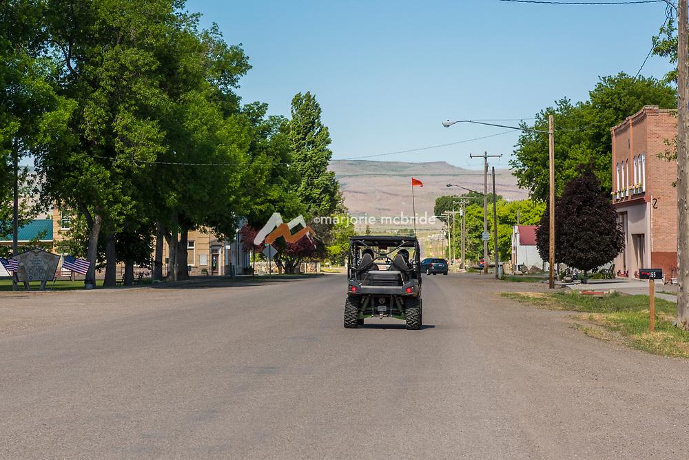 Family in Razor driving ATV past United States Post Office on Main Street in Oakley, Idaho. MR