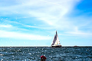 A sailing yacht on Penobscot Bay, in Maine with a red Buoy in the forground with lots of spray coming off the water.