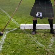Highland Games, 3rd of August 2019, Newtonmore, Scotland, United Kingdom. A strong man gets ready to throw his hammer. To stay firm on the ground his shoes have spikes attached which are firmly dug into the ground. The Highland Games is a traditional annual event where competitors compete as strong men, runners, dancers, pipers and at tug-of-war. The games go back centuries and are happening through-out the summer across Scotland. The games are both an important event locally and a global tourist attraction.