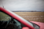 Red car in front of a field with trees on a village close to the city of Svitavy in Czech Republic.