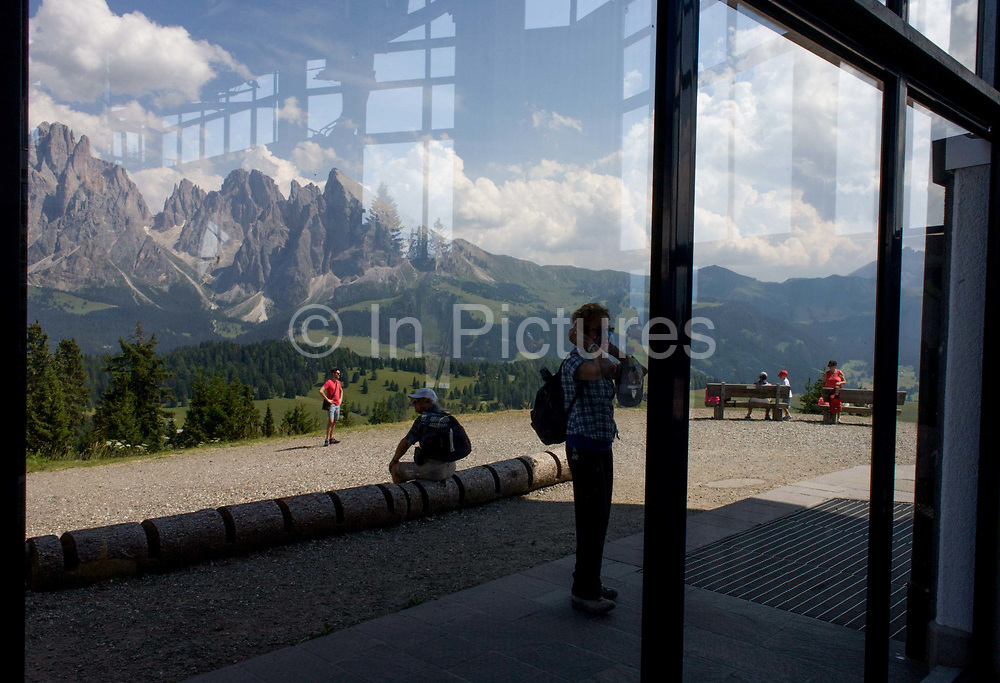 Visitors to the Alpe di Siusi (German: Seiser Alm) at the top of the cable car station at Piz Sorega, above the South Tyrolean town of Ortisei-Sankt Ulrich in the Dolomites, Italy. Standing at the highest point of the vast grassland meadow, they admire the panoramic scenery and await the time to descend again. The Alpe di Siusi is the biggest high-alpine pasture in Europe with a surface of 57 km² and its altitude range from 1680 to 2350 m above sea level. This high-alpine pasture is located in the heart of the Dolomites surrounded by the Sasso Lungo Mountain Group, the Sciliar Nature Park, and the Catinaccio Mountain Group, the Northern Alps and the Sciliar Mountain Massif with Santner Peak.