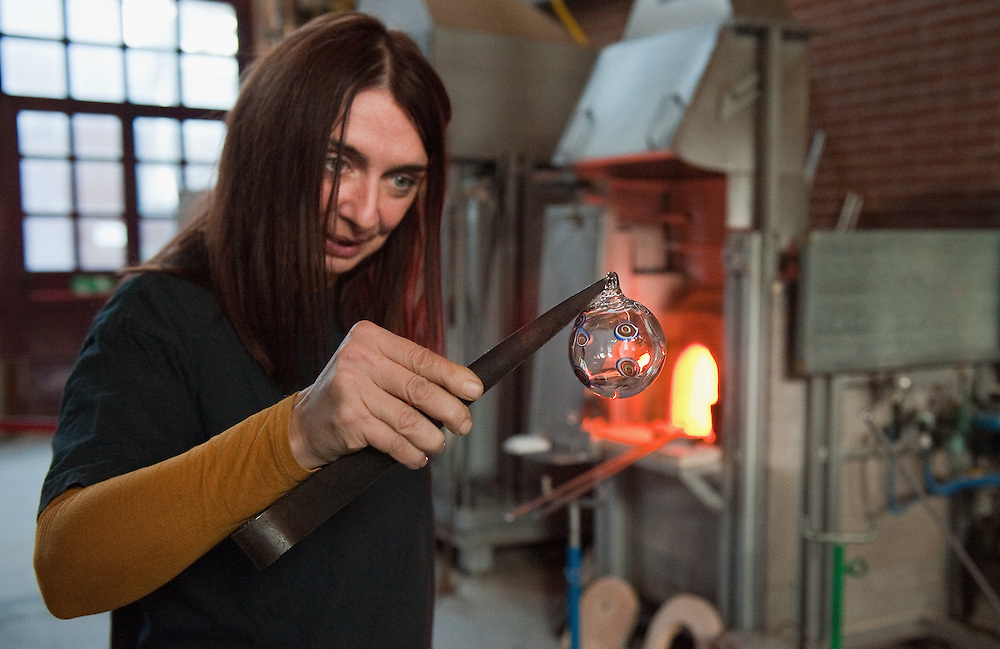 VENICE, ITALY - DECEMBER 18:  Elena Rosso a glass  artist in Murano holds a Christmas bauble next to a  furnace on December 18, 2010 in Venice, Italy. There are only few female glass artists is Italy and they face continuous challanges in a traditionally male dominated field.