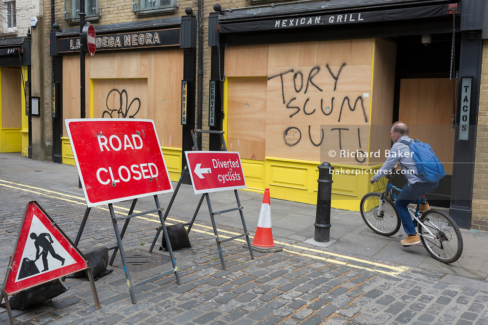 """During the UK's Coronavirus pandemic lockdown and on the day when a further 255 deaths occurred, bringing the official covid deaths to 37,048, <br /> and seen the day after the very unusual press conference by UK Prime Minister's special advisor Dominic Cummings about his breaking of lockdown rules, a cyclist passes the message """"Tory Scum Out!"""" which has been written on plyboard on a closed business in Soho, on 26th May 2020, in London, England."""