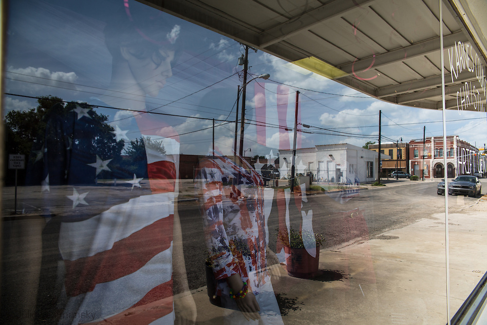 Flag motiff on maniquins at a second hand shop in Kenedy Texas. part of Karnes County in the heart of the Eagle Ford Shale. Despite the fracking industry boom much of the city has closed businesses and blighted buildings.