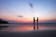 A couple in love face each other at sunset on a beach of Ko Kut, Thailand, Southeast Asia