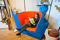 Final-year student Josefina Hägg lounges in one of the designer chairs while reading a book about designing with care.