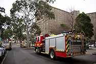 Streets are filled with emergency service vehicles at the main entrance of the Sutton Street housing complex amid the third full day of the total lockdown of 9 housing commission high rise towers in North Melbourne and Flemington during COVID 19.After recording 191 COVID-19 cases overnight forcing Premier Daniel Andrews to announce today that all of metropolitan Melbourne along with one regional centre, Mitchell Shire will once more go back to stage three lockdowns from midnight Wednesday June 8. This comes as the residents of the housing commission towers in North Melbourne and Flemington finish their third day under extreme lockdown, despite only 27 cases being found in the towers. Members of the public gathered outside of the towers this afternoon in support of those trapped inside while riot police arrested two women for standing too close to the fence. While the women were later released, tensions are boiling over both in the towers and out. With 772 active cases in Victoria, NSW closed their border to Victoria effective at midnight tonight.
