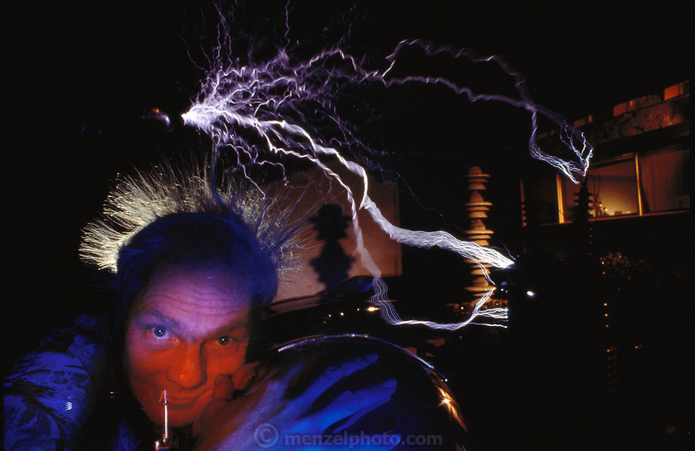 Bill Wysock in his backyard, in Monrovia (near Hollywood), California. Fiery sparks crackle from a metal tube as he also lights a 40-watt light bulb in his hands. He is sitting on a metal disk linked by a cable to his Tesla coil: a transformer producing high-frequency currents that pass safely over the surface of his body. Low-frequency currents would pass through it, meeting resistance and causing injury. MODEL RELEASED (1992)
