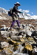 Carol treks towards Chhukhung, Nepal. In the background is Lhotse (27,940 feet), the world's fourth highest peak. The south face of Lhotse rises 3.2 km (1.98 mi) in only 2.25 km (1.4 mi) of horizontal distance (55 degree angle slope), making it the steepest face of this size in the world. Sagarmatha National Park was created in 1976 and honored as a UNESCO World Heritage Site in 1979.
