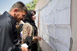 © Licensed to London News Pictures. 30/04/2014. Sulaimaniya, Iraq. Iraqi-Kurdish people search for their names to find out if they are able to vote at a school being used as a polling station during the 2014 Iraqi parliamentary elections in Sulaimaniya, Iraqi-Kurdistan today (30/04/2014). <br /> <br /> The period leading up to the elections, the fourth held since the 2003 coalition forces invasion, has already seen polling stations in central Iraq hit by suicide bombers causing at least 27 deaths. Photo credit: Matt Cetti-Roberts/LNP