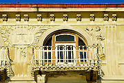Detail of building facade with balcony, arched windows, and intricate figures in bas relief. Opatija, Croatia
