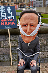 © Licensed to London News Pictures.  29/11/2012. LONDON, UK. An activist from campaign group Avaaz wearing a David Cameron mask protests about the influence of the Murdoch family on British media outside the QE2 Hall in London. The Leveson report into media ethics is due to be released this afternoon. Photo credit :  Cliff Hide/LNP
