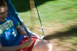 Teenage boy with Autism swinging in a tree,