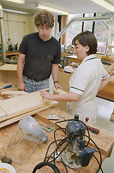 Female occupational therapist supervising male patient in hospital workshop who is making wooden cabinet in preparation for returning to work,