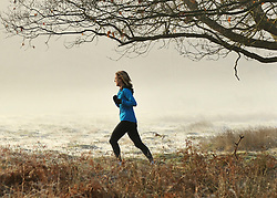 © Licensed to London News Pictures. 15/03/2012. Richmond, UK. A woman jogs through the fog. Foggy conditions at Richmond Park this morning, 15 march 2012. The weather is expected to be good across large parts of the UK for the day.  Photo credit : Stephen SImpson/LNP