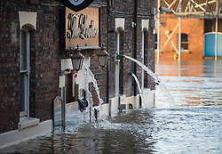 © Licensed to London News Pictures. 29/12/2015. York, UK. Flood water continues to gush from The Lowther pub on the river Ouse in central York. Several warnings of risk to life are sill in place in parts of Lancashire and Yorkshire where rainfall has been unusually high, causing heavy flooding. Photo credit: Ben Cawthra/LNP
